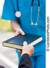 Anciano tomando el libro de la enfermera