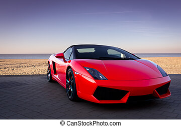 Auto deportivo rojo en la playa del atardecer