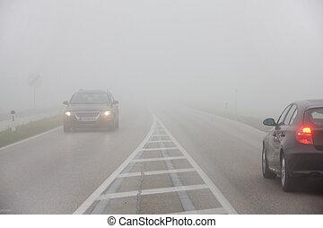Autos en la niebla en un camino