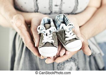 Botas recién nacidas en manos de los padres. Cierra.
