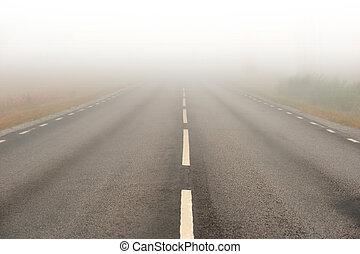 Camino de asfalto con niebla pesada