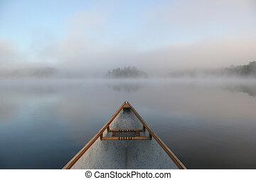 Canoe se inclina sobre un lago húmedo
