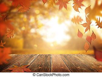 Cayendo hojas de otoño en un fondo de mesa de madera