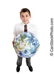 Chico sonriente sosteniendo la tierra del mundo