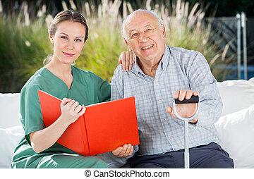 Confiado enfermero femenino y hombre de edad con libro