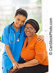 Cuidando a la enfermera africana y al paciente mayor