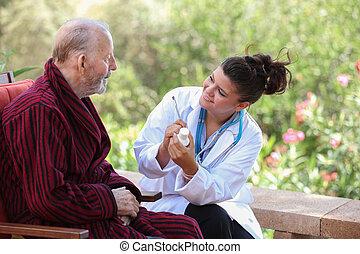 Dr. o enfermera dando medicación a un paciente mayor.
