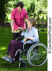 El cuidador le da pera a una anciana discapacitada