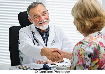 El doctor le da la mano al paciente