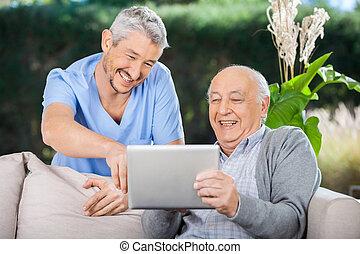 El enfermero y el hombre mayor riéndose mientras usa tableta digital