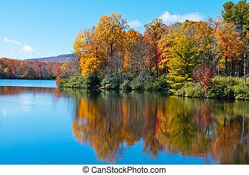 El follaje de otoño se reflejaba en la superficie del lago de precios, en la pista azul