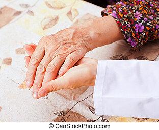 El joven doctor toma las manos de la anciana