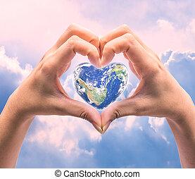 El mundo en forma de corazón con las mujeres manos humanas en un fondo natural borroso el día del corazón del mundo, el elemento de esta imagen provista por la NASA