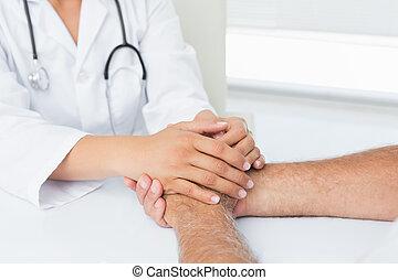 En primer plano de la sección media de un médico sosteniendo a los pacientes de la mano