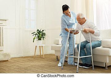Encantadora cuidadora positiva ayudando a su paciente