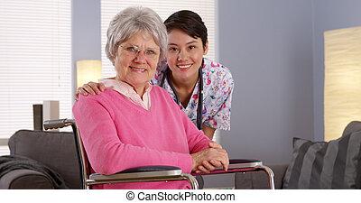 Enfermera asiática sonriendo con un paciente mayor