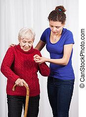 Enfermera ayudando a anciana a caminar