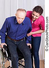 Enfermera ayudando al paciente discapacitado