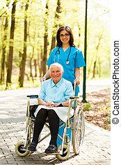 Enfermera con anciana en silla de ruedas
