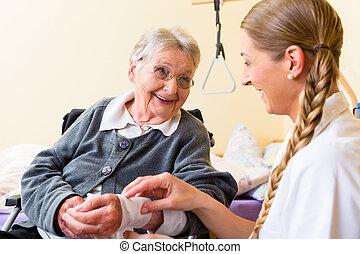 Enfermera cuidando a una anciana en el asilo