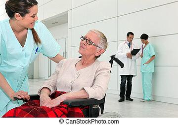 Enfermera hablando con una anciana en silla de ruedas