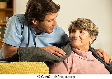 Enfermera masculina preocupándose por el jubilado