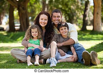 Familia feliz sentada en el jardín