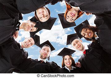 Felices graduados multiétnicos formándose acurrucándose contra el cielo