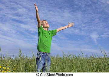 Feliz niño cristiano brazos levantados en oración.