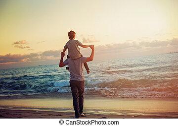 Feliz padre e hijo pasándolo bien en la playa en la luz del atardecer