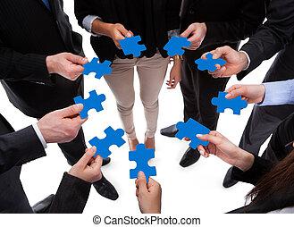 Gente de negocios que conecta piezas de rompecabezas