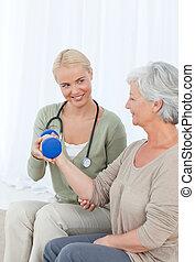 Hermosa enfermera ayudando a su paciente a hacer ejercicios