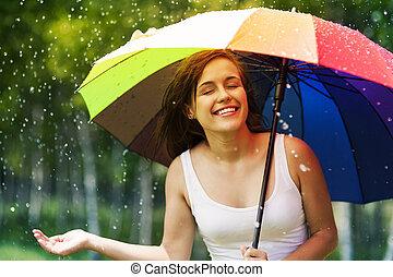 Hermosa mujer disfrutando de la lluvia de verano