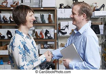 Hombre de negocios estrechando manos con vendedor de zapatos