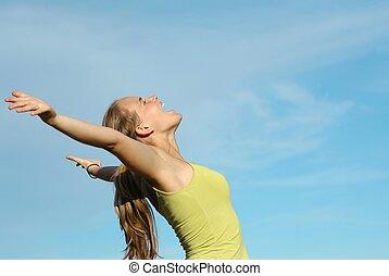 Jovencita gritando o cantando brazos levantados con fe y alabanza