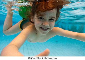 La chica sonríe, nadando bajo el agua en la piscina