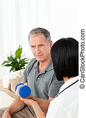 La enfermera ayuda a su paciente a hacer ejercicios