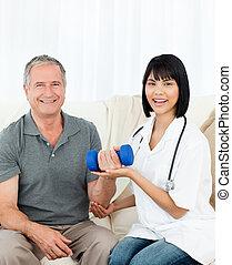 La enfermera ayudando a su paciente a hacer exe