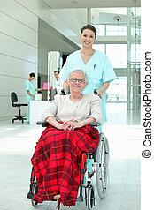 La enfermera del hospital empujando a una anciana en una silla de ruedas