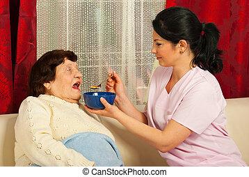 La enfermera le da sopa a la anciana