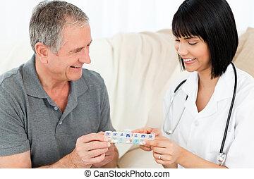 La enfermera le muestra pastillas a su paciente