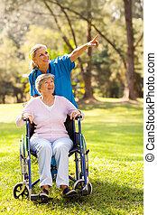 La enfermera lleva a un paciente discapacitado a dar un paseo