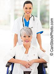 La enfermera médica cuidando a un paciente en silla de ruedas