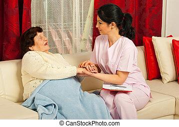 La enfermera reconforta a la anciana enferma