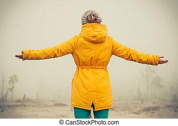 La joven con las manos levantadas disfrutando del estilo de vida al aire libre y las emociones de la felicidad concepto de la naturaleza nublada del invierno en el fondo