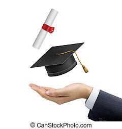 La mano del empresario sosteniendo un sombrero de graduación y un diploma