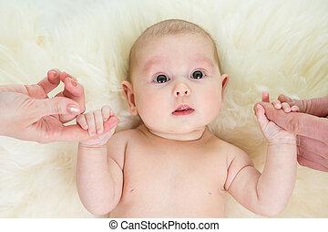 La niña con las manos de los padres en la cama de piel