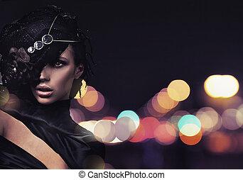 La señora de la moda sobre el fondo de la ciudad