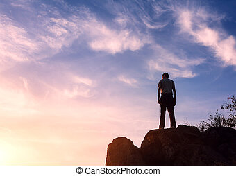 La silueta de un hombre al atardecer en la montaña