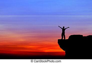 La silueta de un hombre en la roca al atardecer
